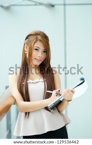 Portrait of young business woman standing near window in modern office and writing notes