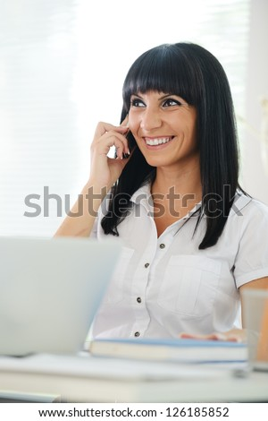 Portrait of young business woman using laptop at office and speaking on cell phone