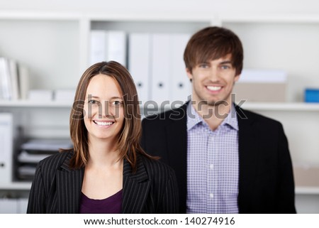 Portrait of young businessman and businesswoman standing in office