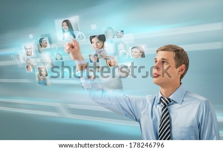 Portrait of young businessman choosing people for his business team using virtual computer interface - stock photo