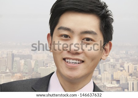 Portrait of young businessman close-up, cityscape in background - stock photo