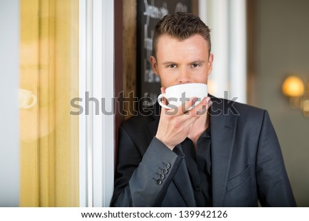 Portrait of young businessman drinking coffee at restaurant - stock photo