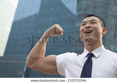 Portrait of young businessman flexing muscle outdoors - stock photo