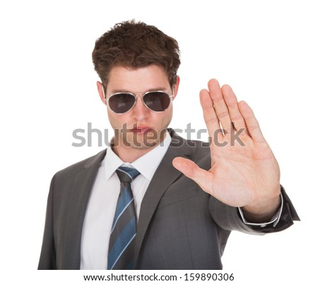 Portrait Of Young Businessman Gesturing On White Background