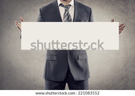 Portrait of young businessman in suit holding white sticker or signboard in his hands. Elegant man in business suit with tie advertising smth with blank paper for text message.  - stock photo