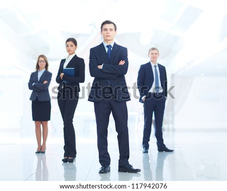 Portrait of young businessman looking at camera with elegant partners on background - stock photo