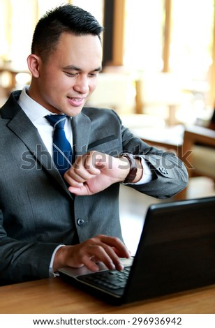 portrait of young businessman looking at his watches - stock photo
