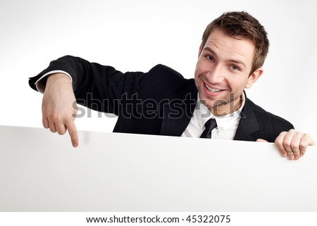 Portrait of young businessman pointing at blank white sign