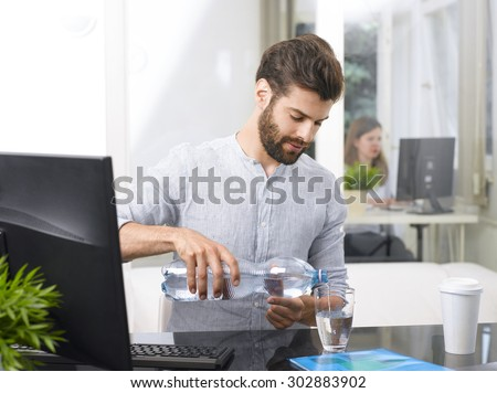 Portrait of young businessman sitting at his working place and pouring water into a glass. - stock photo