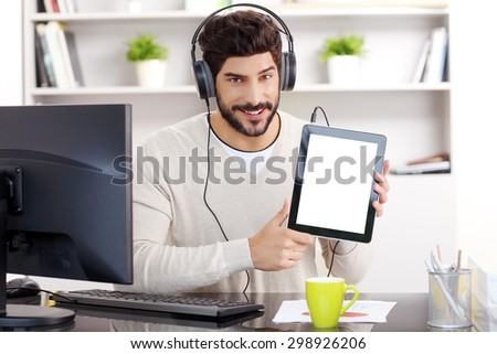 Portrait of young businessman sitting at his working place in front of his computer. Professional man with headphone holding hands digital tablet while downloading music from internet.  - stock photo
