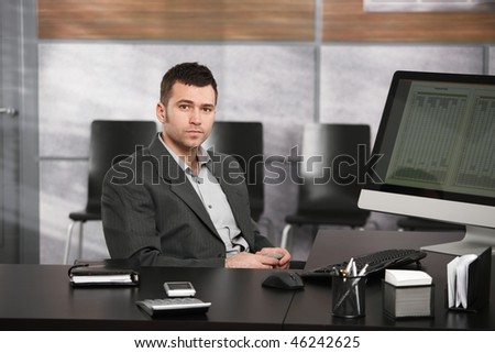 Portrait of young businessman sitting at office desk, holding mobile phone, looking at camera. - stock photo