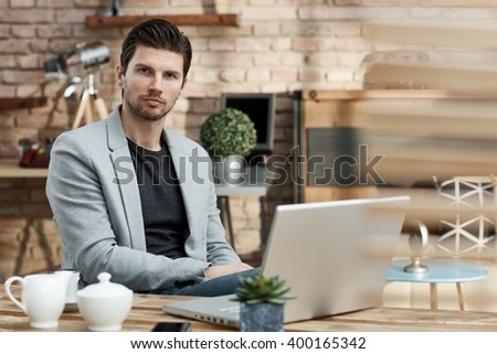 Portrait of young businessman sitting at table, having laptop. - stock photo