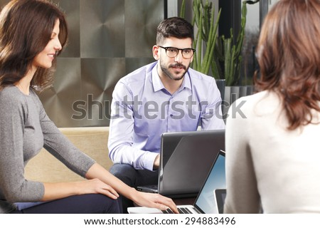 Portrait of young businessman sitting in front of personal computer and presenting his idea to businesswomen. Business people working together while sitting at business meeting at office.  - stock photo