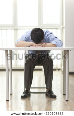 Portrait of young businessman sleeping in office