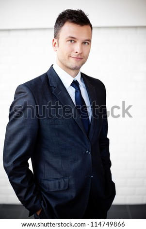 Portrait of young businessman standing agains the wall - stock photo