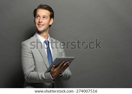 portrait of young businessman thinking while holding a tablet isolated on grey background with copy space - stock photo