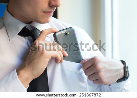 Portrait of young businessman using his mobile phone in office.