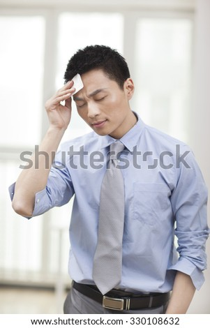 Portrait of young businessman wiping forehead - stock photo