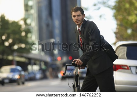Portrait of young businessman with bicycle on urban street - stock photo