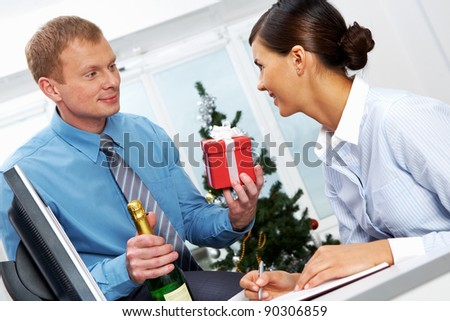 Portrait of young businessman with bottle of champagne giving present to his colleague - stock photo