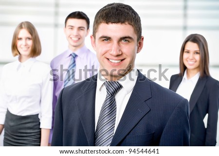 Portrait of young businessman with cheerful team in background