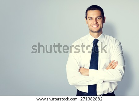 Portrait of young businessman with crossed arms pose, with blank copyspace area for text or slogan, specially toned - stock photo