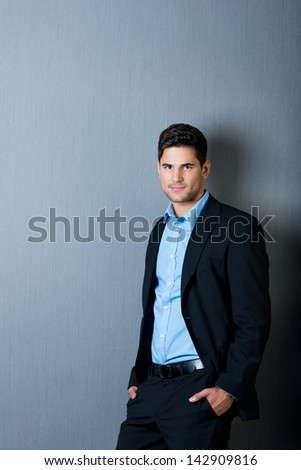Portrait of young businessman with hands in pockets leaning on blue wall - stock photo