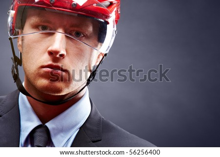Portrait of young businessman with hockey helmet on head - stock photo
