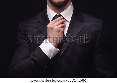 Portrait of young businessmans suit isolated on dark background - stock photo