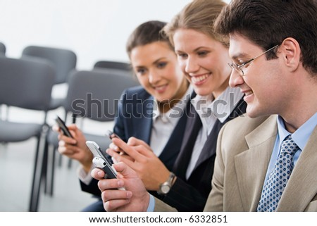 Portrait of young businesspeople exchanging an information on the mobile phones - stock photo