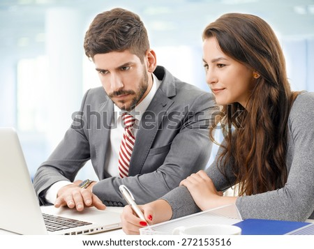 Portrait of young businesswoman and businessman sitting at desk in front of laptop and working on new project. Teamwork at office.