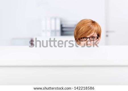 Portrait of young businesswoman behind cubicle in office - stock photo