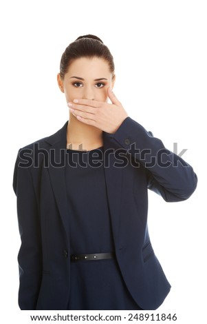 Portrait of young businesswoman covering with hand her mouth - stock photo