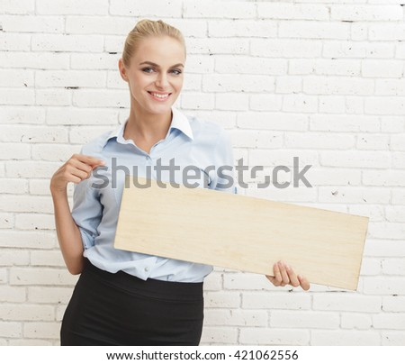 portrait of young businesswoman holding and pointing at blank board with white brick wall background - stock photo