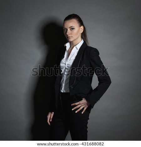 Portrait of young businesswoman in black suit on dark background
