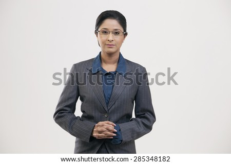Portrait of young businesswoman in suit isolated over gray background - stock photo