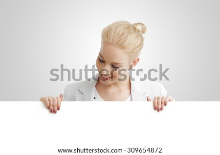 Portrait of young businesswoman smiling and holding white blank sign billboard.