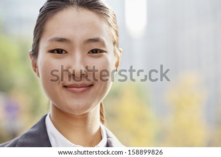 Portrait of young businesswoman smiling outside in Beijing - stock photo