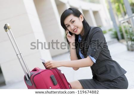 Portrait of young businesswoman speaking on the phone outside - stock photo