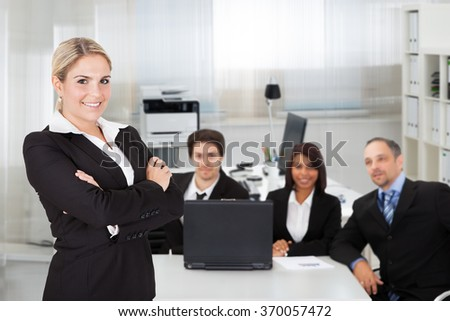 Portrait of young businesswoman standing arms crossed while colleagues sitting at desk in office