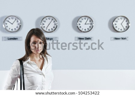 Portrait of young businesswoman standing with world time zone clocks in background - stock photo