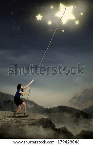 Portrait of young businesswoman taking stars from the sky space - stock photo