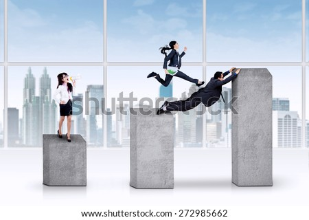 Portrait of young businesswoman using a megaphone to lead her team through business chart - stock photo