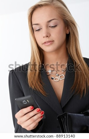 Portrait of young businesswoman using smart phone, texting.? - stock photo