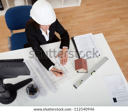 Portrait of young businesswoman wearing hardhat with blueprints at office desk - stock photo