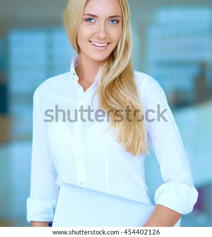 Portrait of young businesswoman with laptop in office with colleagues in the background - stock photo