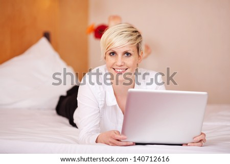 Portrait of young businesswoman with laptop while lying on bed - stock photo