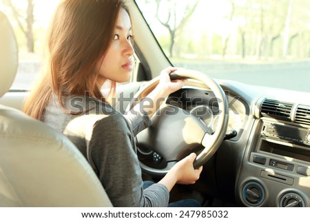 portrait of young bussinesswoman driving a car - stock photo