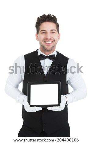 Portrait of young butler displaying digital tablet over white background - stock photo