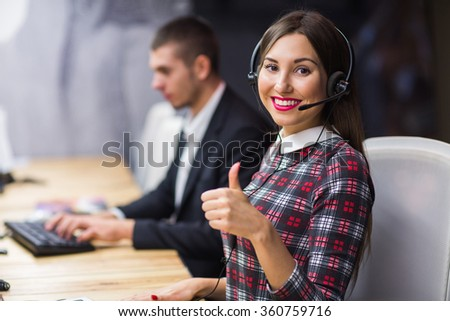 Portrait of young call center operator wearing headset with colleagues working in background at office - stock photo